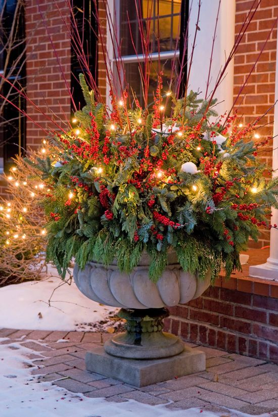 08-oversized-urn-with-evergreens-faux-berries-and-red-branches-is-glowing-up-thanks-to-the-lights