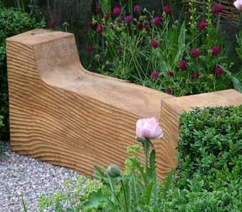 деревянная садовая скамейка среди цветов