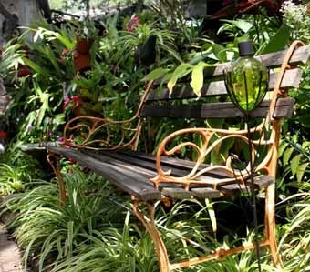 садовая скамейка в укромном уголке среди кустов