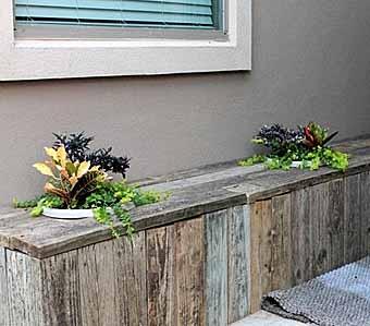 скамейка с цветочными контейнерами около дома