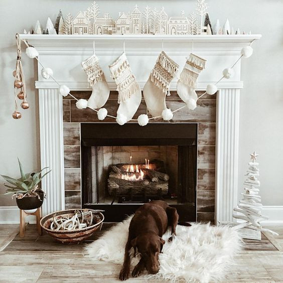 22 a mantel styled with metallic jingle bells and a white pompom garland for Christmas