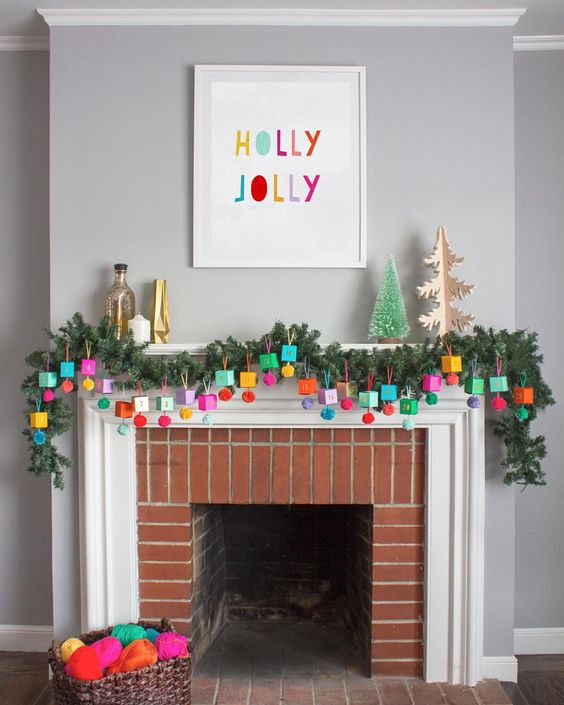 24 an advent calendar made of colorful boxes and pompoms hanging ona lush evergreen garland