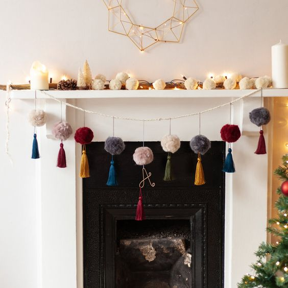 26 colorful pompom and tassel garland plus a garland of white pompoms on the mantel