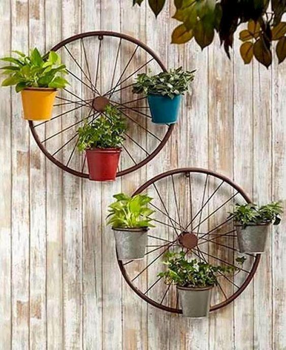 Колеса от велосипеда с кашпо на стене